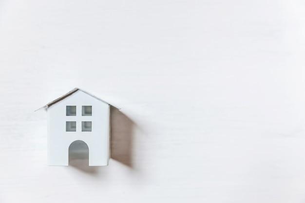 Einfach minimales design mit miniaturspielzeughaus lokalisiert auf weißem hintergrund