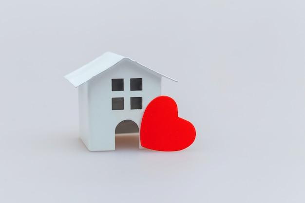 Einfach minimales design mit weißem spielzeugminiaturhaus mit dem roten herzen lokalisiert auf weiß