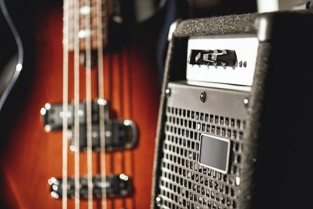 Einfach perfekter klang. nahaufnahme einer braunen e-gitarre und eines verstärkers, die im tonstudio stehen. musikkonzept. musikanlage. musikinstrumente.