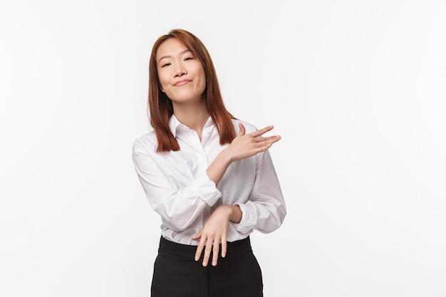 Einfach. sorgloser und ungestörter asiatischer profi, die schultern mit erfreutem, entspanntem ausdruck abbürsten, projekt als keine große sache abschließen, leicht erfolg erzielen,