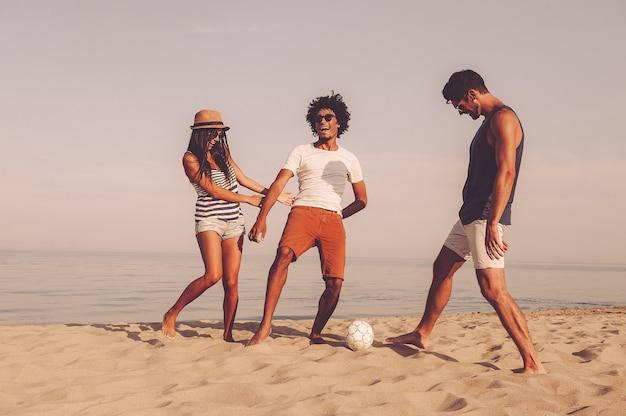 Einfach spaß haben. drei fröhliche junge leute, die mit fußball am strand mit meer im hintergrund spielen