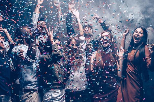 Einfach spaß haben. gruppe schöner junger leute, die beim tanzen buntes konfetti werfen und glücklich aussehen