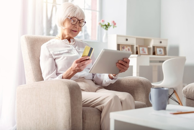 Einfach und bequem. entzückende ältere frau, die im bequemen sessel sitzt und online-einkauf macht, bereit, mit ihrer kreditkarte zu zahlen