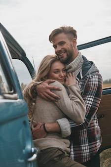 Einfach verliebt. schönes junges paar, das umarmt und lächelt, während es im freien nahe dem retro-art-minivan steht