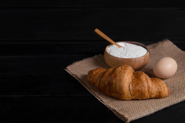 Einfache croissants, mehlschale und rohe eier auf dunkler holzoberfläche. hochwertiges foto