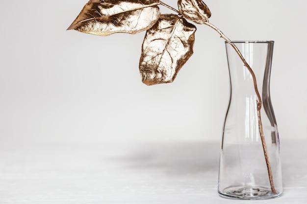 Einfache glasvase mit ast des baumes und hellen goldfarbenen blättern auf weißem tisch. moderne heimdekorationsanlage.