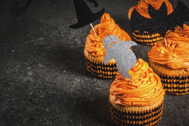 Einfache idee der lustigen kinderfestlichkeit für halloween: kürbiskuchen mit sahne, mit dekorationen in form von feiertagssymbolen - geist, hexe, schläger. auf einem schwarzen copyspace