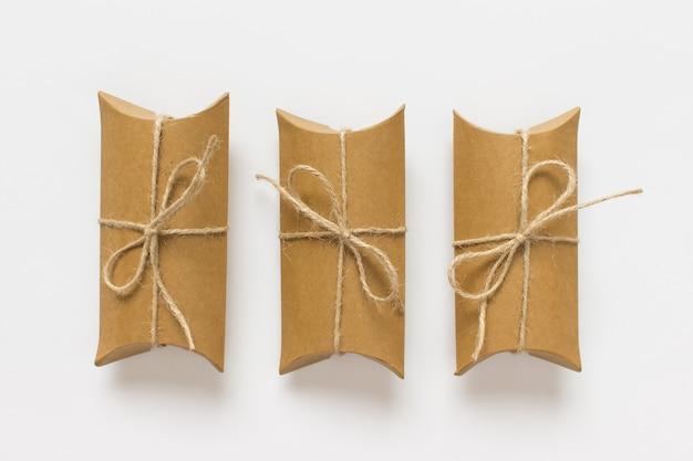 Einfache komposition mit drei geschenken präsentiert schachteln aus bastelpapier, die mit packfaden auf weißem hintergrund gebunden sind.
