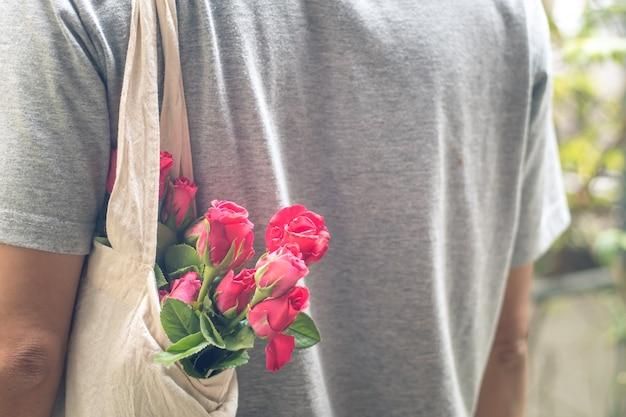 Einfache liebe mann tragen rosen in der weißen tasche, valentinsgruß-tageshintergrund, hochzeitstag