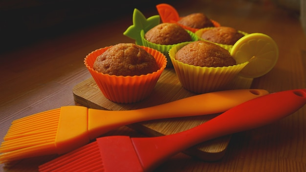 Einfache mini-muffins in bunten silikon-backformen. cupcakes aus silikon zum backen und silikonbürsten. küchen- und kochkonzept auf holzhintergrund