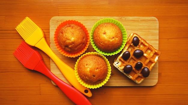 Einfache mini-muffins in bunten silikon-backformen und waffeln. küchen- und kochkonzept auf holzhintergrund