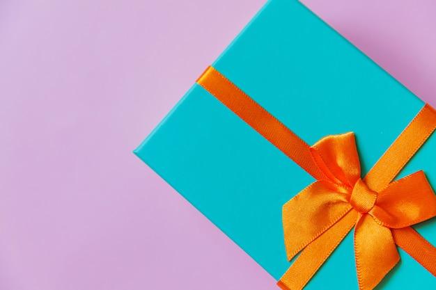 Einfache minimale design blaue geschenkbox lokalisiert auf violettem lila buntem hintergrund