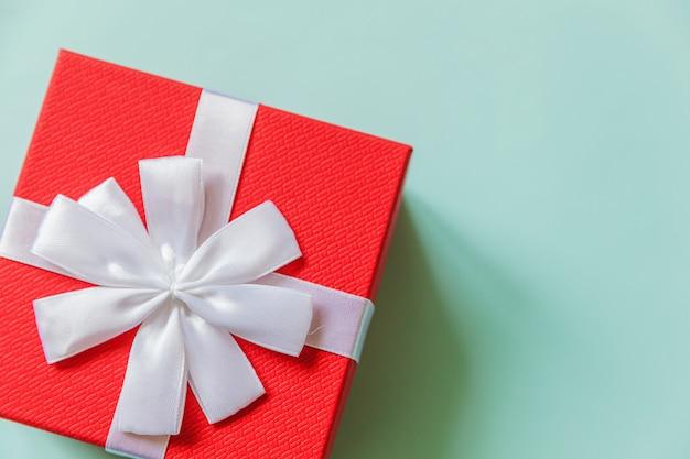 Einfache minimale rote geschenkbox des designs lokalisiert auf buntem hintergrund des pastellblauen