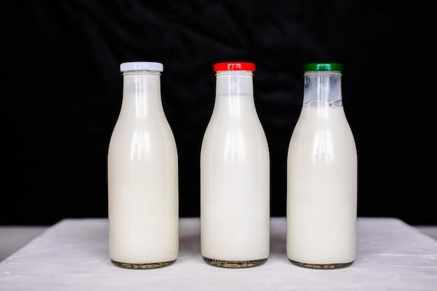 Einfache vintage glasflaschen mit frischer milch, kefir und joghurt.
