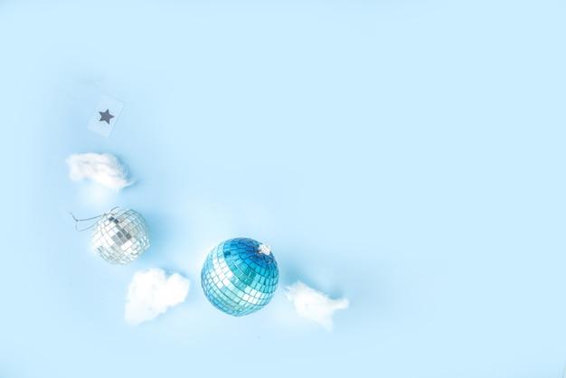 Einfache weihnachtsgrußkarte, partyeinladung, verkauf abstraktes flatlay mit disco-weihnachtskugeln und lichtbrett, auf hellblauem hintergrund kopienraum draufsicht