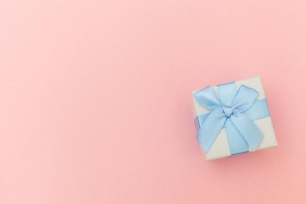 Einfache weiße geschenkbox des minimalen entwurfs lokalisiert auf buntem pastellrosa-tisch