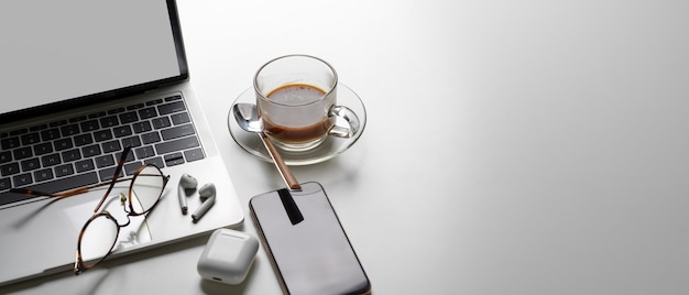 Einfacher arbeitsbereich mit kopierbereich, modell-laptop, kaffeetasse, kopfhörer, smartphone und brille