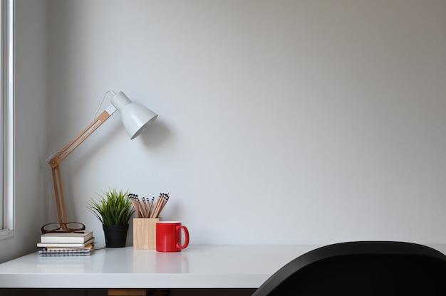 Einfacher arbeitsbereich mit lampe, pflanze, kaffeetasse und kopierraum auf weißem tisch.