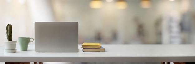 Einfacher arbeitsbereich mit laptop, kaktustopf, becher, büchern und kopierraum