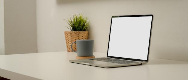 Einfacher arbeitsbereich mit modell-laptop, kaffeetasse, baumkanne und kopierraum auf weißem tisch