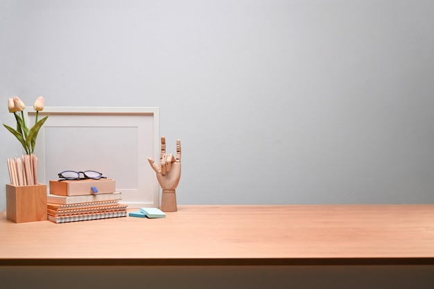 Einfacher arbeitsplatz mit bleistifthalter, büchern und leerem bilderrahmen auf holztisch.