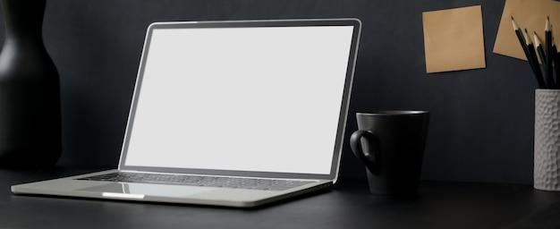 Einfacher arbeitstisch mit leerem bildschirm laptop, kaffeetasse, briefpapier und dekoration auf schwarzem tisch