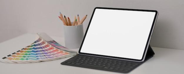 Einfacher arbeitstisch mit tablet, buntstiften und farbfeld auf weißem schreibtisch