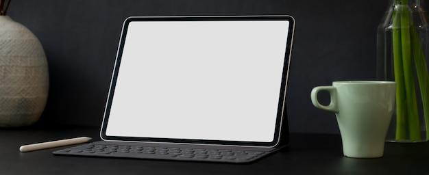 Einfacher arbeitstisch mit tablett mit leerem bildschirm, kaffeetasse und pflanzenvasen auf schwarzem tisch