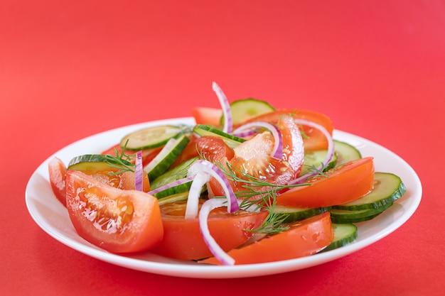 Einfacher gemüsesalat von tomate, gurke, zwiebel und dill im weißen teller auf hellrotem hintergrund.