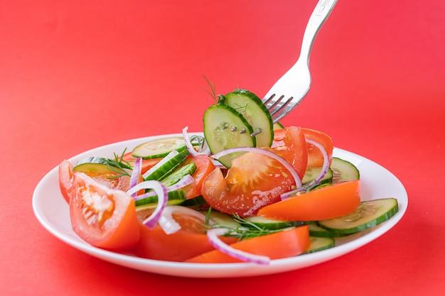 Einfacher gemüsesalat von tomaten, gurken, zwiebeln und dill im weißen teller auf hellrotem hintergrund.
