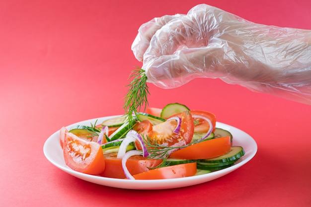 Einfacher gemüsesalat von tomaten, gurken, zwiebeln und dill in der weißen platte auf hellrotem hintergrund.