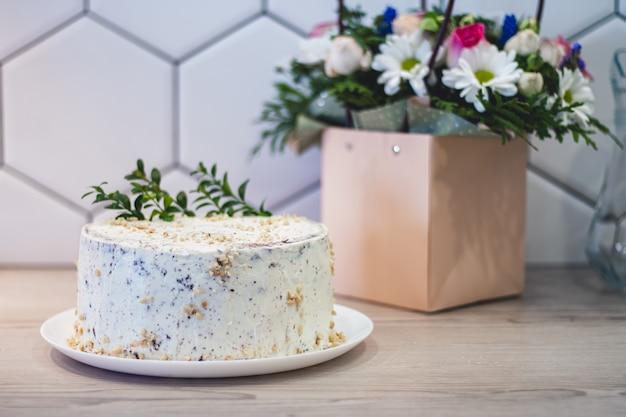 Einfacher hausgemachter weißer kuchen mit nüssen auf der küchenarbeitsplatte auf dem hintergrund eines straußes verschiedener blumen in einer papiertüte mit griffen