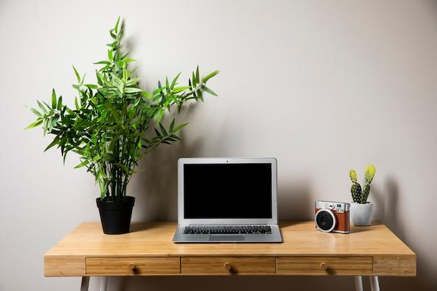 Einfacher hölzerner schreibtisch mit grauem laptop