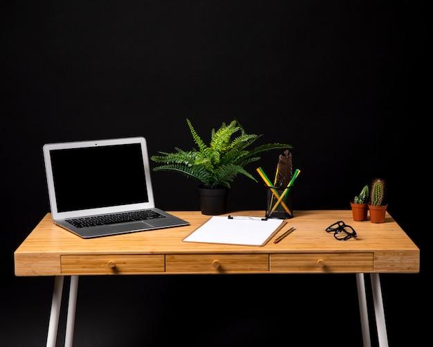 Einfacher hölzerner schreibtisch mit klemmbrett und laptop
