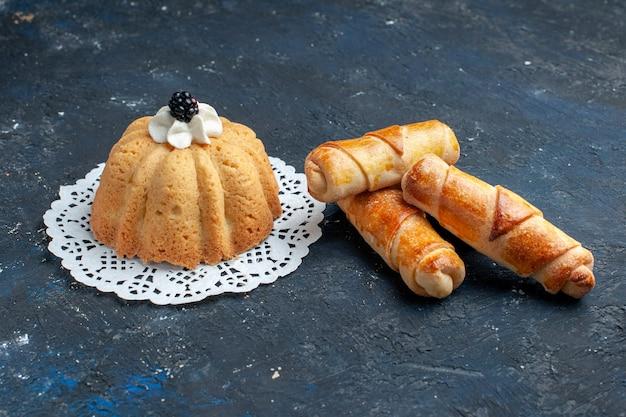 Einfacher leckerer kuchen mit sahne und brombeere zusammen mit armreifen auf dunklem schreibtisch