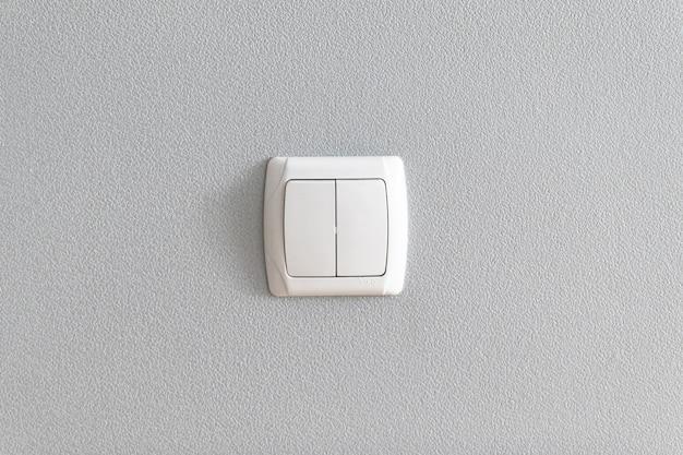 Einfacher lichtschalter an grauer wand.