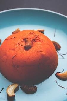 Einfacher oder safran gewürzter grieß oder soji halwa, auch bekannt als sweet rava sheera oder shira - indisches fest süß garniert mit trockenfrüchten. serviert in einem teller oder einer schüssel, selektiver fokus