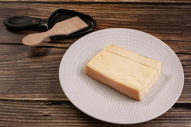 Einfacher raclettekäse in einem weißen teller auf einem holztisch