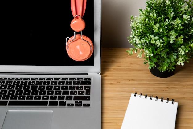 Einfacher schreibtisch mit laptop und kopfhörern