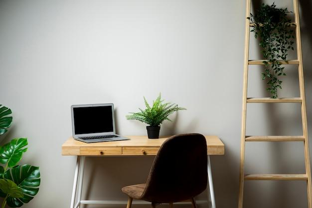 Einfacher schreibtisch mit stuhl und grauem laptop