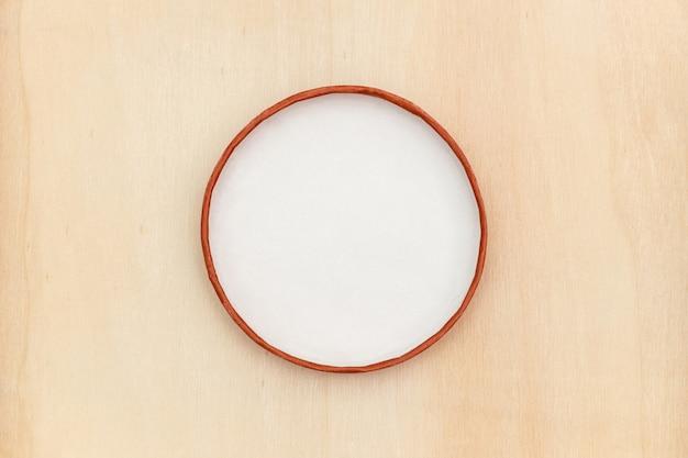 Einfacher weißer kreisrahmen auf holzoberfläche Premium Fotos