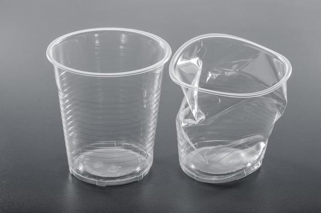 Einfacher weißer nagelneuer und zerknitterter plastikbecher auf grauem hintergrund, nahaufnahme. recycling-konzept.
