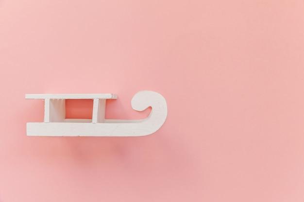 Einfacher weißer schlitten der minimalen entwurfszusammensetzung lokalisiert auf dem bunten trendigen hintergrund des rosa pastells