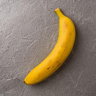 Einfaches bild der einzelnen reifen gelben banane auf grauem metallischem hintergrund