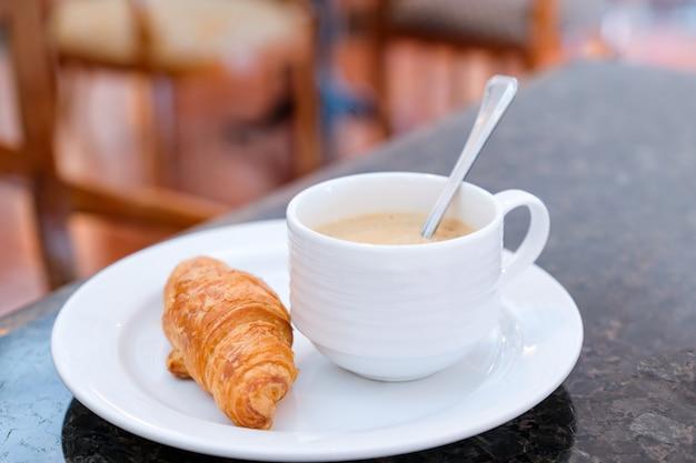 Einfaches frühstück am morgen mit croissant und heißem kaffee.