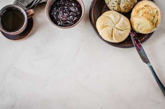 Einfaches frühstück: kaffee americano, frische brötchen und marmelade.