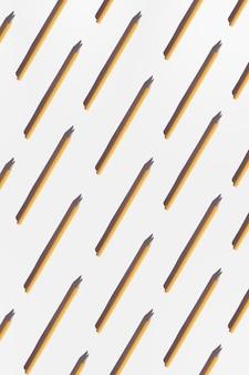Einfaches gelbes büro-bleistiftmuster mit harten schatten auf dem weiß