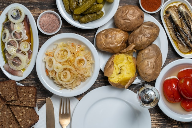 Einfaches rustikales ukrainisches essen auf holztisch, nahaufnahme, draufsicht. vielzahl von gekochtem gemüse und speisen in tellern, ukraine