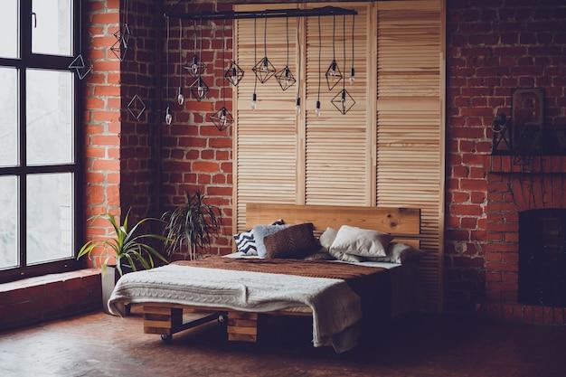 Einfaches schlafzimmer mit doppelbett, roter backsteinmauer und großem fenster