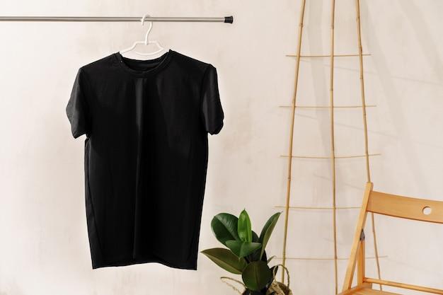 Einfaches schwarzes baumwoll-t-shirt auf kleiderbügel für ihr design, kopienraum